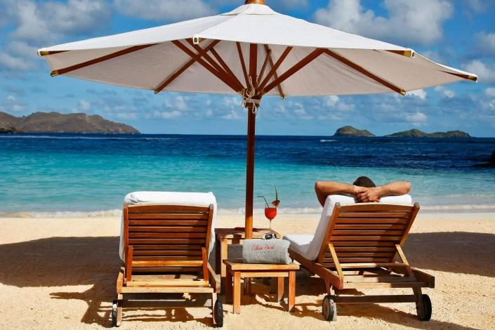 Photo de détente sur une plage avec parasol et matelas