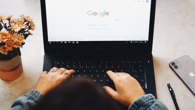 tatooed womens fingers typing on windows 10 laptop google apple iphone