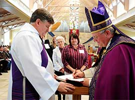 Bishop David L. Ricken of Green Bay, Wis., signs the Book of Elect during the Rite of Election of catechumens and Call to Continuing Conversion of candidates at Our Lady of Lourdes Church in De Pere, Wis., in 2014. CNS photo/Sam Lucero, The Compass