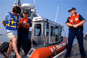 Adult male being arrested by USCG officers for boating under the influence