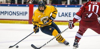 March 19, 2016: Quinnipiac Bobcats defenseman Connor Clifton (4) skates with the puck as Harvard Crimson forward Brayden Jaw (10) tries to defend during 2016 ECAC Tournament Championship game between Harvard University and Quinnipiac University at Herb Brooks Arena in Lake Placid, NY. (John Crouch/J. Alexander Imaging)