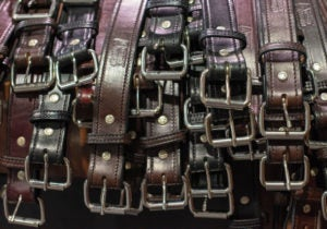 A pile of black and brown leather gun belts.