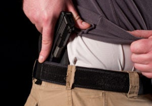 A man lifts the lower hem of his gray sweater to reval his white undershirt amd a small IWB holster from which he is drawing a small black pistol.