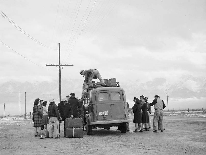 Internees wait to be trucked to the Manzanar War Relocation Center, in California.