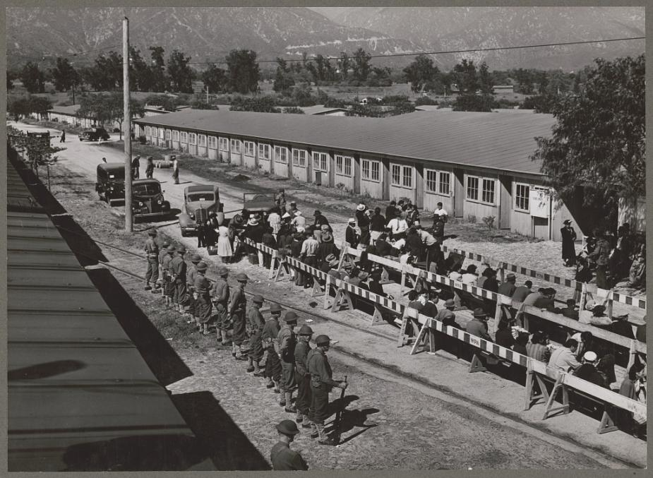 Japanese Americans are guarded at Santa Anita registration center. Uncleaned horse stables at the Southern California racetrack were used for temporary housing.