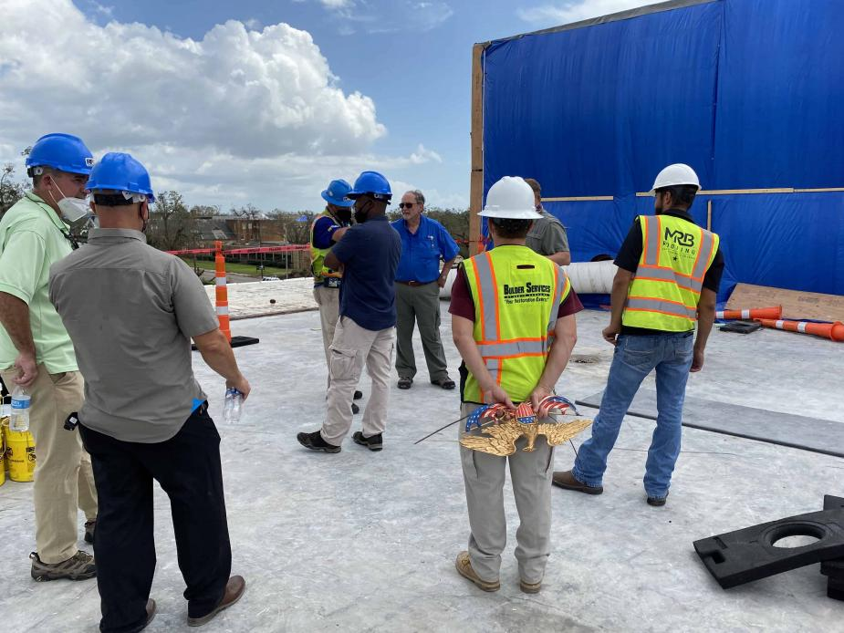 """Chief Judge S. Maurice """"Maury"""" Hicks (center, in blue shirt) inspects the roof of the Lake Charles courthouse."""