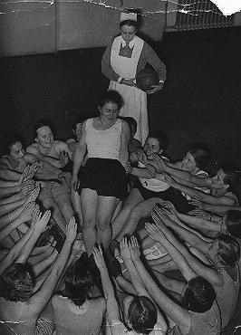 Members of the Nazi girls' organization, the League of German Girls (BDM), do a group exercise. Dresden, Germany, December 1936.