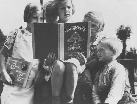 "German children read an anti-Jewish propaganda book titled DER GIFTPILZ ( ""The Poisonous Mushroom""). The girl on the left holds a companion volume, the translated title of which is ""Trust No Fox."" Germany, ca. 1938."