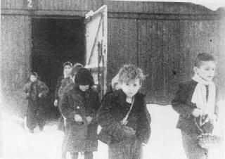 Poco después de su liberación, niños sobrevivientes de Auschwitz caminan fuera de sus barracas. Polonia, posterior al 27 de enero de 1945.