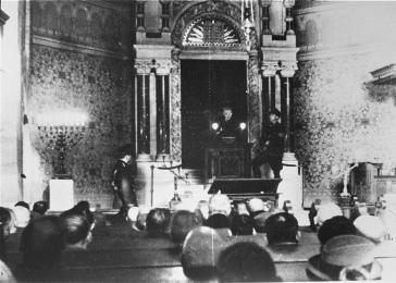 Members of the Jewish community of Baden-Baden are compelled to sit in the synagogue and listen while selections from Hitler's Mein Kampf are read aloud from the bimah (lecturn).