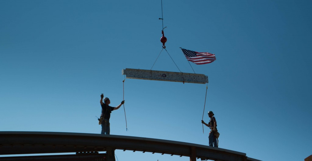 Workers guide the final beam to the Teaching Theatre at the topping-off ceremony Thursday.  Photo by NIGEL MEYER/The Shield