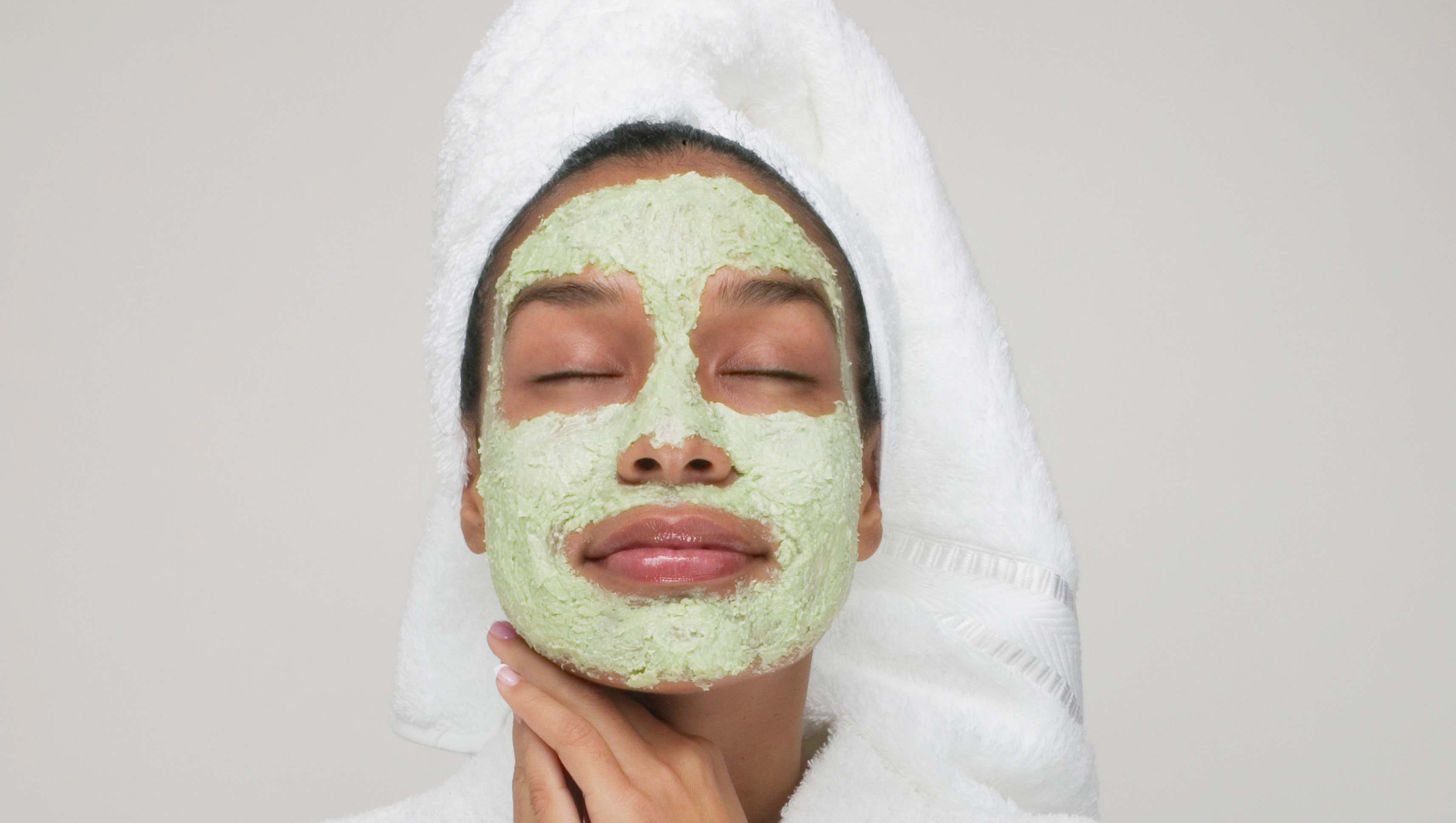 woman wearing a green face mask and white towel spa