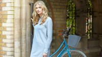 Young woman standing beside bicycle.