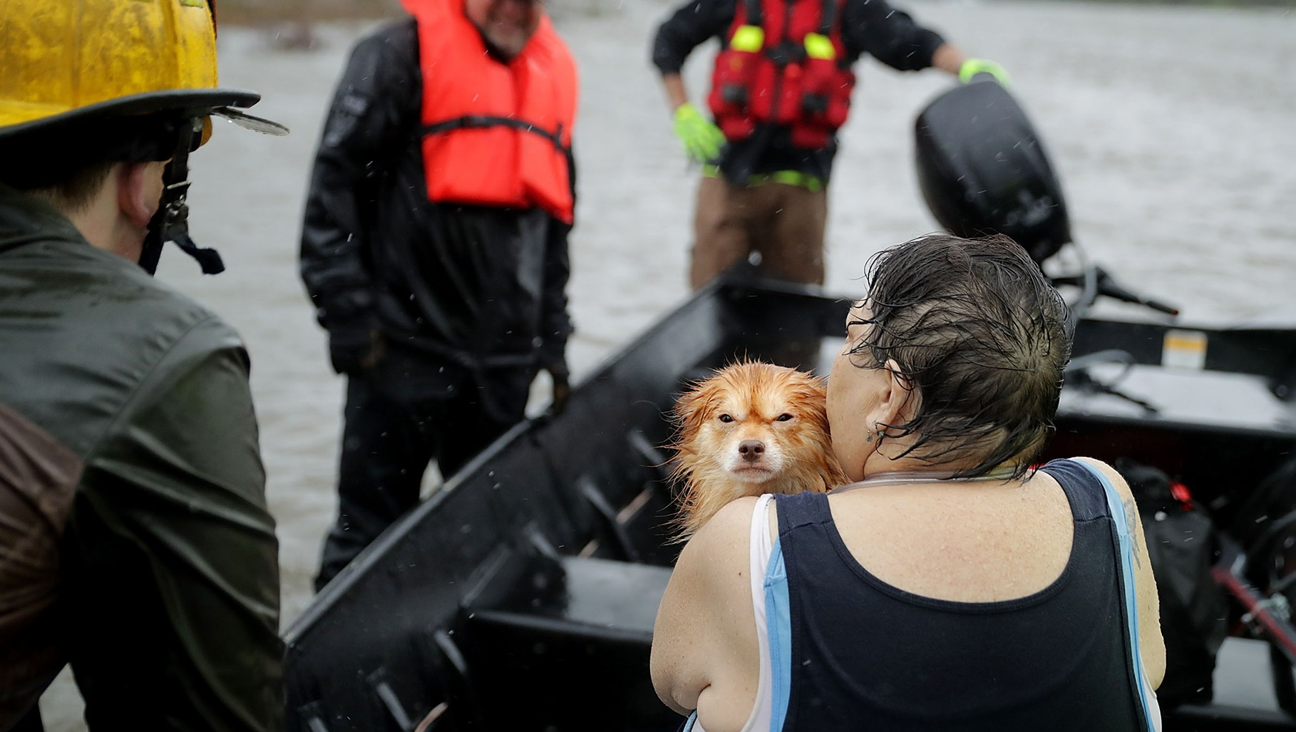 Rescue workers from Township No. 7 Fire Department and volunteers from the Civilian Crisis Response Team use a boat to rescue a woman and her dog from their flooded home during Hurricane Florence