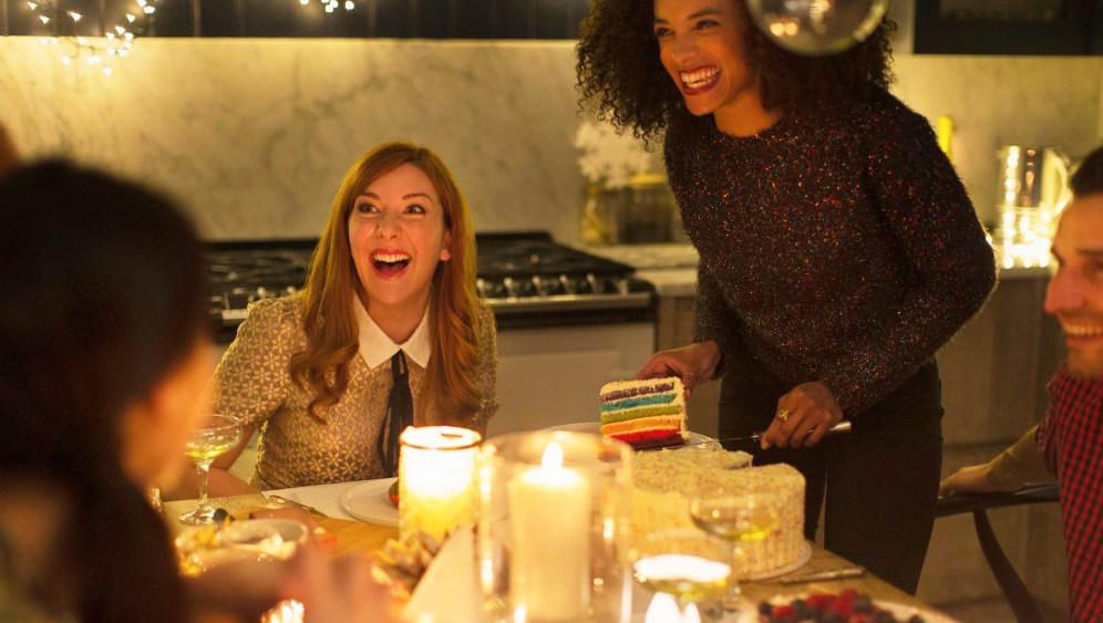 Laughing friends enjoying cake at candlelight Christmas dinner party