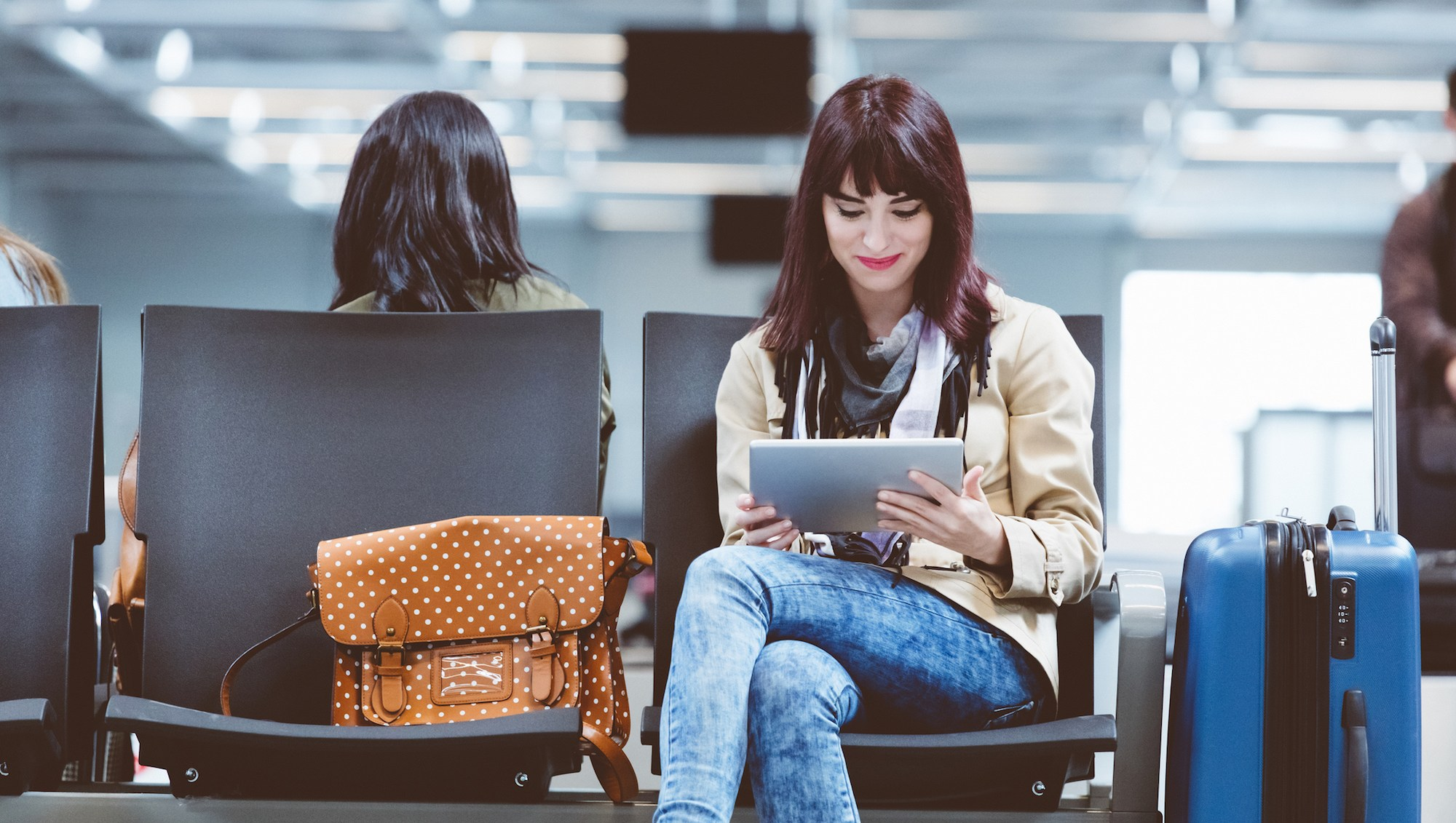 Young woman using tablet pc at airport