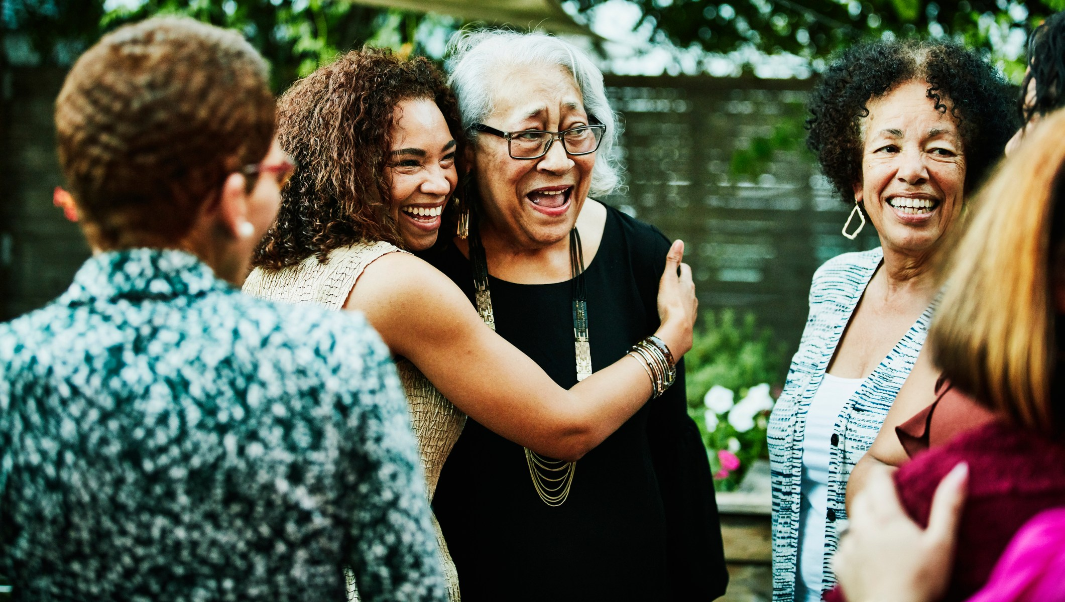 Mature daughter embracing senior mother after outdoor family dinner party