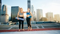 women holding yoga mats and exercising on roof