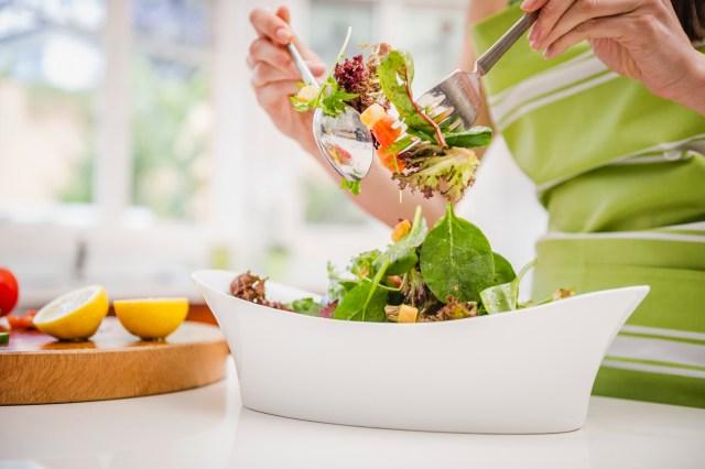 Hispanic woman tossing salad in domestic kitchen