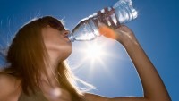 Woman drinking water, low angle view against sky with sun