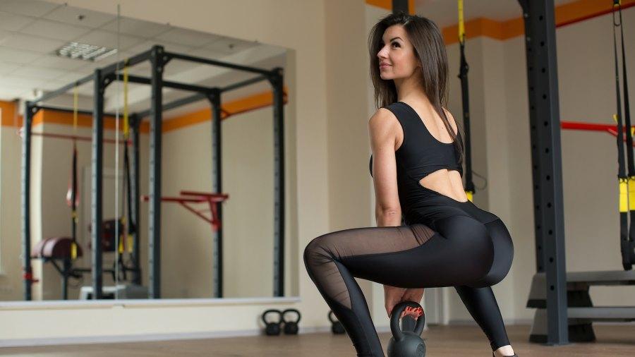 Woman-Squatting-In-Leggings-Stock-Photo