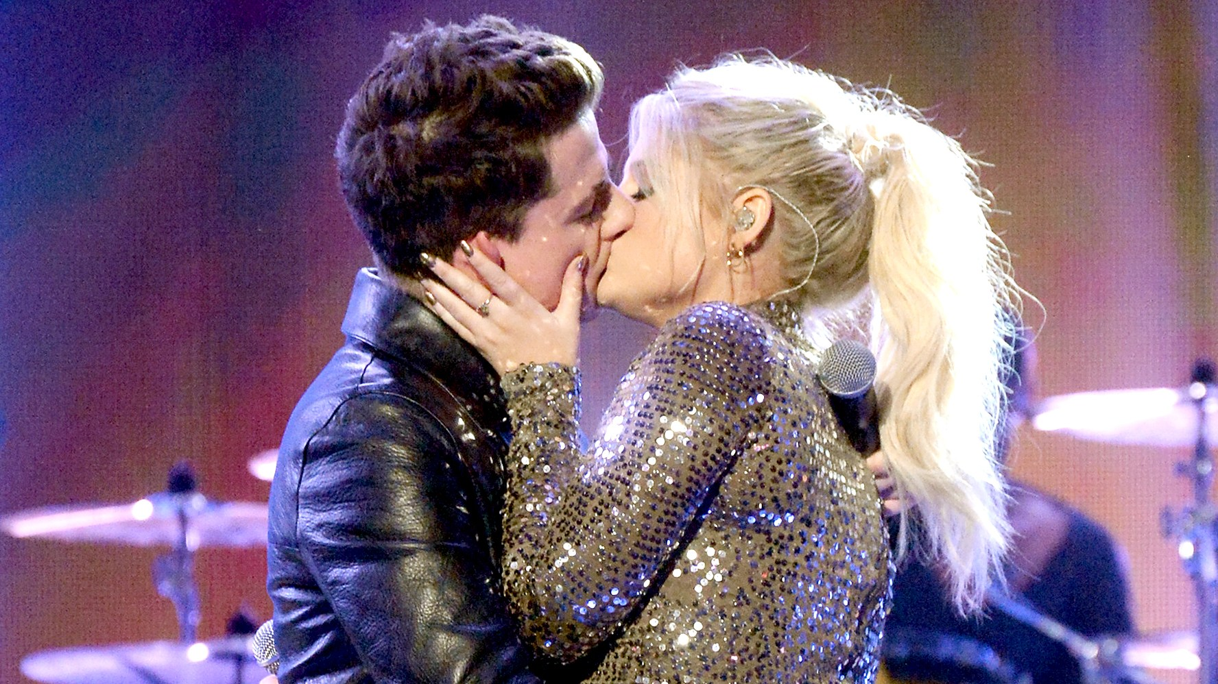 Charlie Puth and Meghan Trainor kiss onstage during the 2015 American Music Awards.