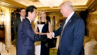 Japanese Prime Minister Shinzo Abe, front left, shakes hands with U.S. President-elect Donald Trump during a meeting as Ivanka Trump, back right, the oldest daughter of Donald Trump, and her husband, Jared Kushner, back left.