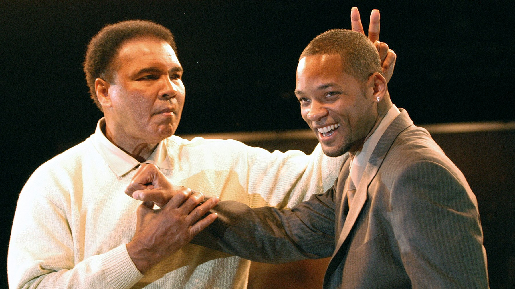 Muhammad Ali gestures behind the head of actor Will Smith at the Miami Art Basel Taschen book premiere of Ali's new book, 'GOAT - Greatest Of All Time' at the Miami Convention Center December 6, 2003 in Miami, Florida.