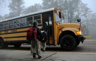 Children boarding a school bus in the early morning