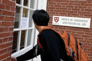 A freshman enters the admissions and financial aid building at Harvard University.