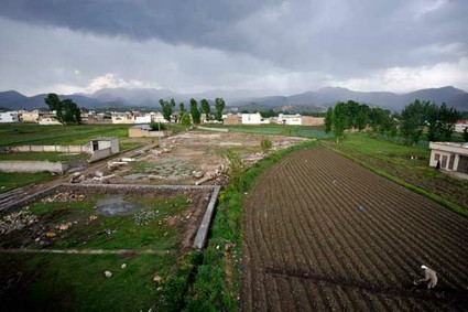 A Pakistani farmer works in his field near the site of the demolished compound of slain al-Qaeda leader Osama bin Laden in Abbottabad.