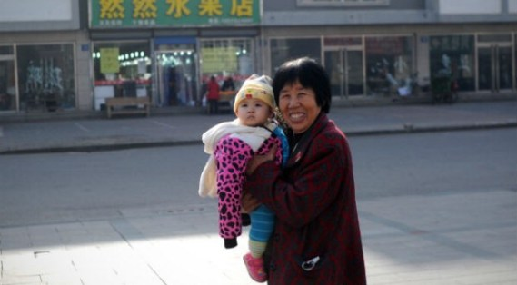 A woman holds a baby as she walks along a road in Tangshan, in northern China's Hebei province on Nov. 15, 2013.