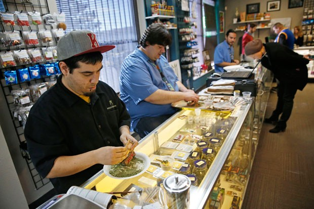 Employees roll joints behind the sales counter at Medicine Man marijuana dispensary, which is to open as a recreational outlet at the start of 2014, in Denver, Friday Dec. 27, 2013.