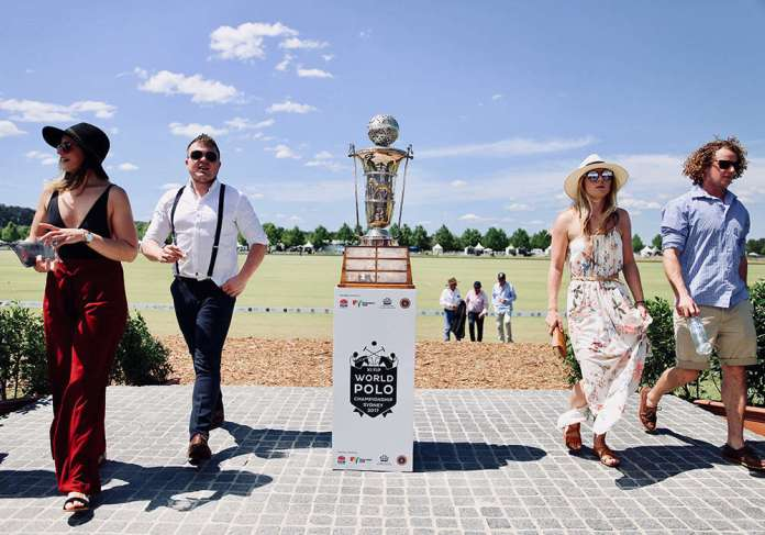 Spectators stroll next to the FIP World Polo Championship trophy at Sydney Polo Club in Richmond NSW, Australia.