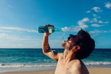 thirst man on beach drinking water
