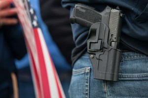 OLYMPIA, WA - JANUARY 19: A demonstrator carries a handgun while listening to speakers at a pro-gun rally on January 19, 2013 in Olympia, Washington. The Guns Across America national campaign drew thousands of protesters to state capitols, including over 1,000 in Olympia. (Photo by David Ryder/Getty Images)
