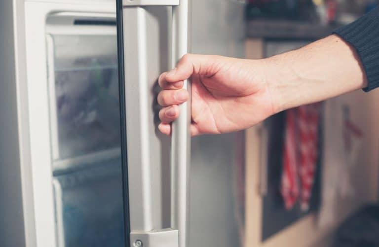 Persona che apre un congelatore verticale