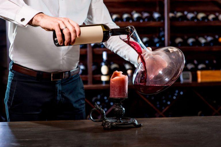 Uomo che versa il vino nel decanter