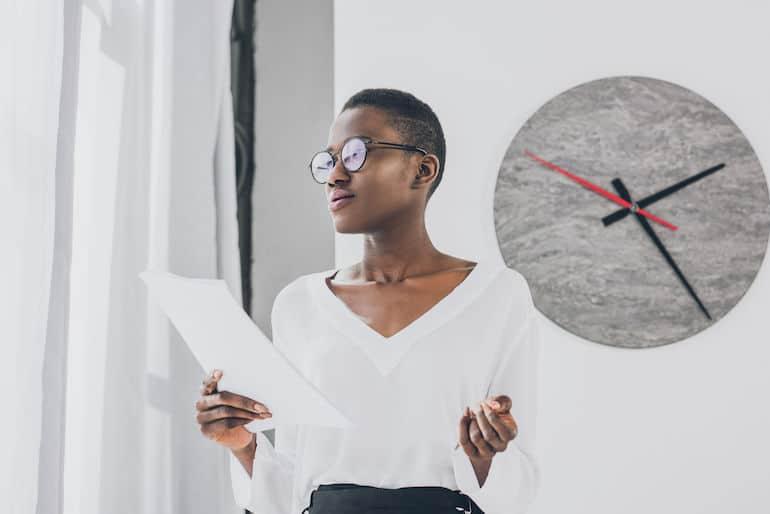 Donna di colore con ampio orologio da parete sullo sfondo