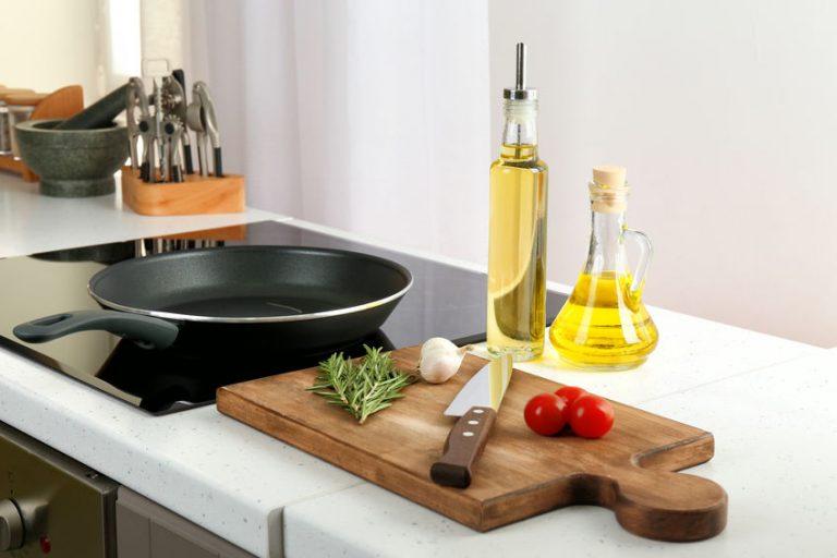 Padella per induzione con olio e verdure vicino