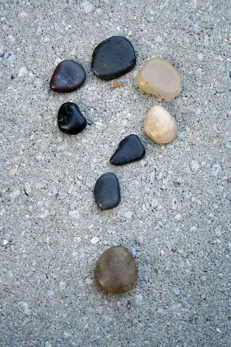 Stenar utlagda på en grusväg i formen av ett frågetecken.