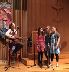 Photo from the 2018 UUC Talent Show - Megan playing guitar, three girls singing