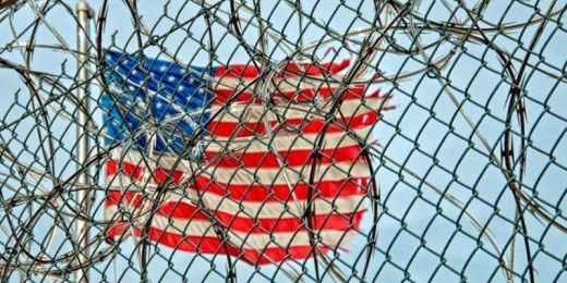 U.S. flag behind razor wire fence