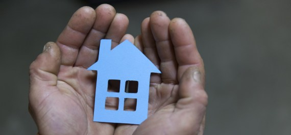 Rough cupped hands gently holding a cardboard cutout of a house