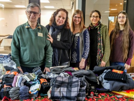 UUC volunteers with piles of warm clothes donated by UUC congregants for Teen Feed - December 2019