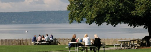 Dumas Bay Center - people at outside tables near shore