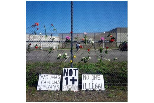 Flowers and signs at the Northwest Detention Center fence
