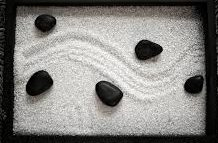 White sand with curving track and black rocks