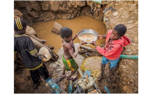Three boys with containers next to a muddy water hole