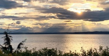 Rays of light streaming through early sunset clouds over Puget Sound with Olympics in the background